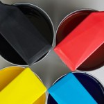 Four cans of printing ink - red, black, yellow, blue