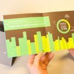 """Designer's hands holding """"Books"""" spread from Groover Design promo book, yellow & green with white text on brown"""